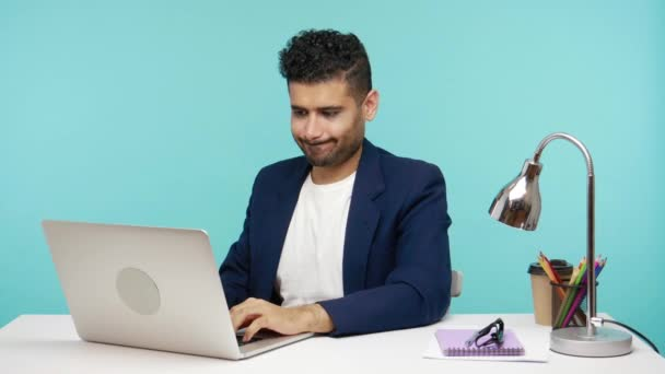Strict bearded male boss in business suit showing thumbs down checking work of his subordinates, dissatisfied with internet connection quality. Indoor studio shot isolated on blue background
