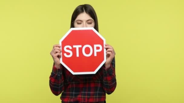Ernste, konzentrierte Frau im karierten Hemd, in der Hand ein rotes Stoppschild, das vor Gefahren warnt, leugnet schlechte Angewohnheit. Indoor Studio aufgenommen isoliert auf gelbem Hintergrund