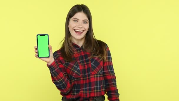 Extremely happy satisfied brunette woman in checkered shirt holding green screen smartphone and red sale card, satisfied with discounts in application. Indoor studio shot isolated on yellow background