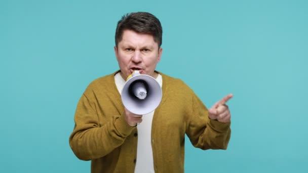 Vážné agresivní muž středního věku hlasitě mluví v megafonu, dělat oznámení, dirigování setkání, požadování rovnosti práv, osvobození. Vnitřní studio záběr izolované na modrém pozadí