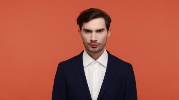 Porträt eines gutaussehenden brünetten Mannes im Anzug, der Schweigegegeste zeigt und um Schweigen bittet, blickt mit zitternder Miene in die Kamera. Indoor Studio isoliert auf orangefarbenem Hintergrund aufgenommen.
