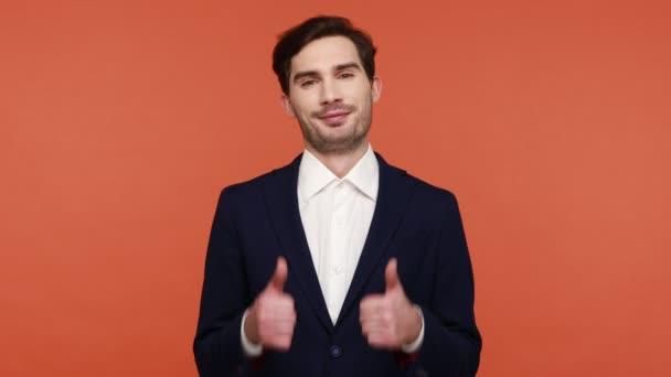 Dobrá práce, dobrá práce! Vzrušený pozitivní muž s vousy a tmavými vlasy ukazující palce nahoru a usmívající se, oslavující úspěch, oblečený v obchodním obleku. Vnitřní studio záběr izolované na oranžovém pozadí.