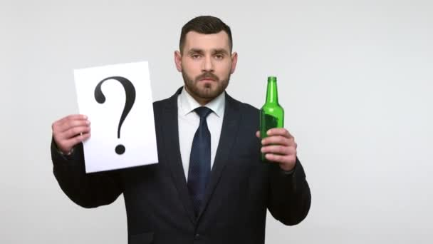 Portrait of younfg adult bearded businessman in black official style suit holding with paper mark and alcohol bottle, drink or choose healthy lifestyle. Indoor studio shot isolated on gray background.