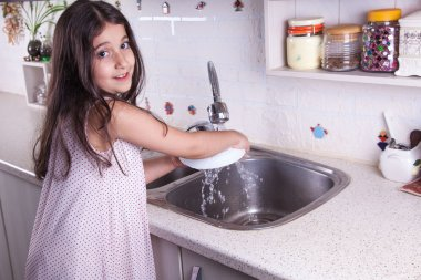 One beautiful middle eastern little girl with pink dress and long dark brown hair and eyes on white kitchen,helping parents to wash dishes and drinking water and smiling looking at camera.