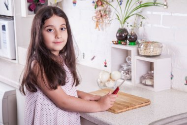 Beautiful little middle eastern 7 years old girl is working with knife and onion in the white kitchen.