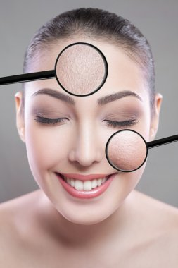 Skin care and beauty concept - face of beautiful young woman with smile over gray background. skin defect on face by loupe. closed eyes looking at camera.