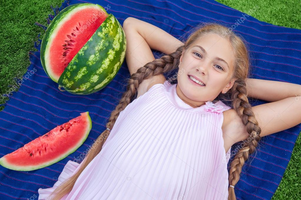 Cute little girl eating watermelon on the grass in summer time. with ponytail long hair and toothy smile sitting on grass and enjoying.