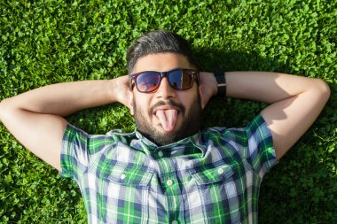 One funny fashion middle eastern man with beard and fashion hair style is resting on beautiful green grass day time. young arab businessman 20-30 years, resting after hard work looking at camera..