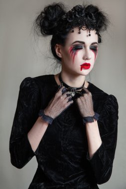 Young beautiful gothic woman with white skin and red lips. Halloween makeup.