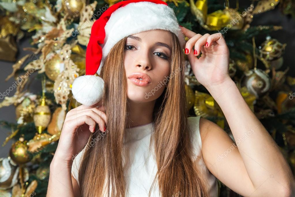 Young funny beautiful fashion model with dark eyes, brown hair and santa hat celebrating new year at home. new year decoration, with positive emotion posing and  looking at camera. yellow gold decor