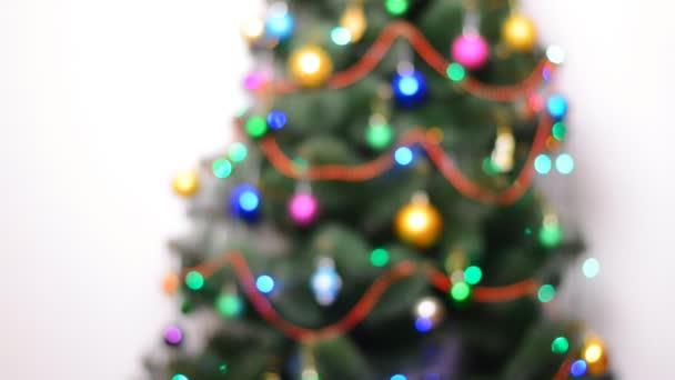 Homályos zöld karácsonyfa, ajándékok és a Bulbes villogni