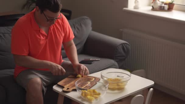 Caucasian man peeling potato at home, cooking dinner. Father or single man preparing food