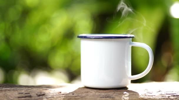 weiße Emaille Kaffeebecher auf dem Gasherd grünen Wald Bokeh Hintergrund