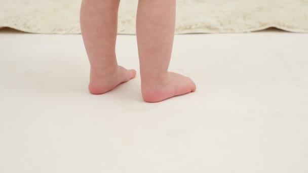 Dívčí nožičky na bílém koberci zblízka. Zpomalený pohyb.