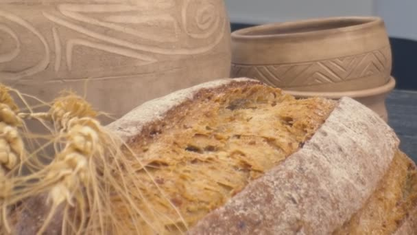 Close-up of freshly baked whole grain bread against the backdrop of a ceramic clay jug move in slow motion.