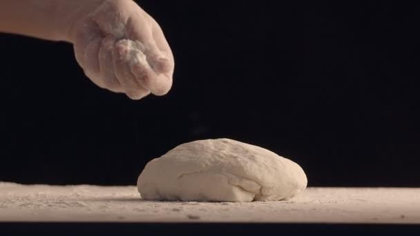 Männliche Hände bestreuen ein Stück Backteig mit Mehl. Teig liegt auf einem Holztisch. Gefilmt auf schwarzem Hintergrund.