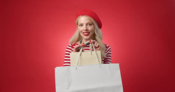 Young woman 20s in red beret hold hands pointing on package bags with purchases after shopping isolated red background studio. People lifestyle concept. Happy woman with shopping bags dreamed
