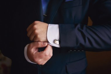 Hands of wedding groom getting ready in suit