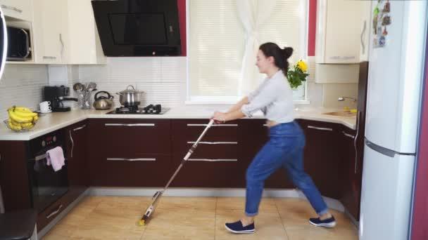 Eine gut gelaunte junge Hausfrau putzt die Küche und tanzt mit einem Wischmopp. 4k
