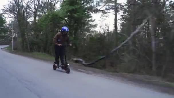 Ein Fahrer mit Schutzhelm und einem leistungsstarken Elektroroller fährt einen Waldweg entlang. Ein Mann fährt mit einem Elektroroller im Wald auf einer Betonstraße von der Seite der Kamera aus.