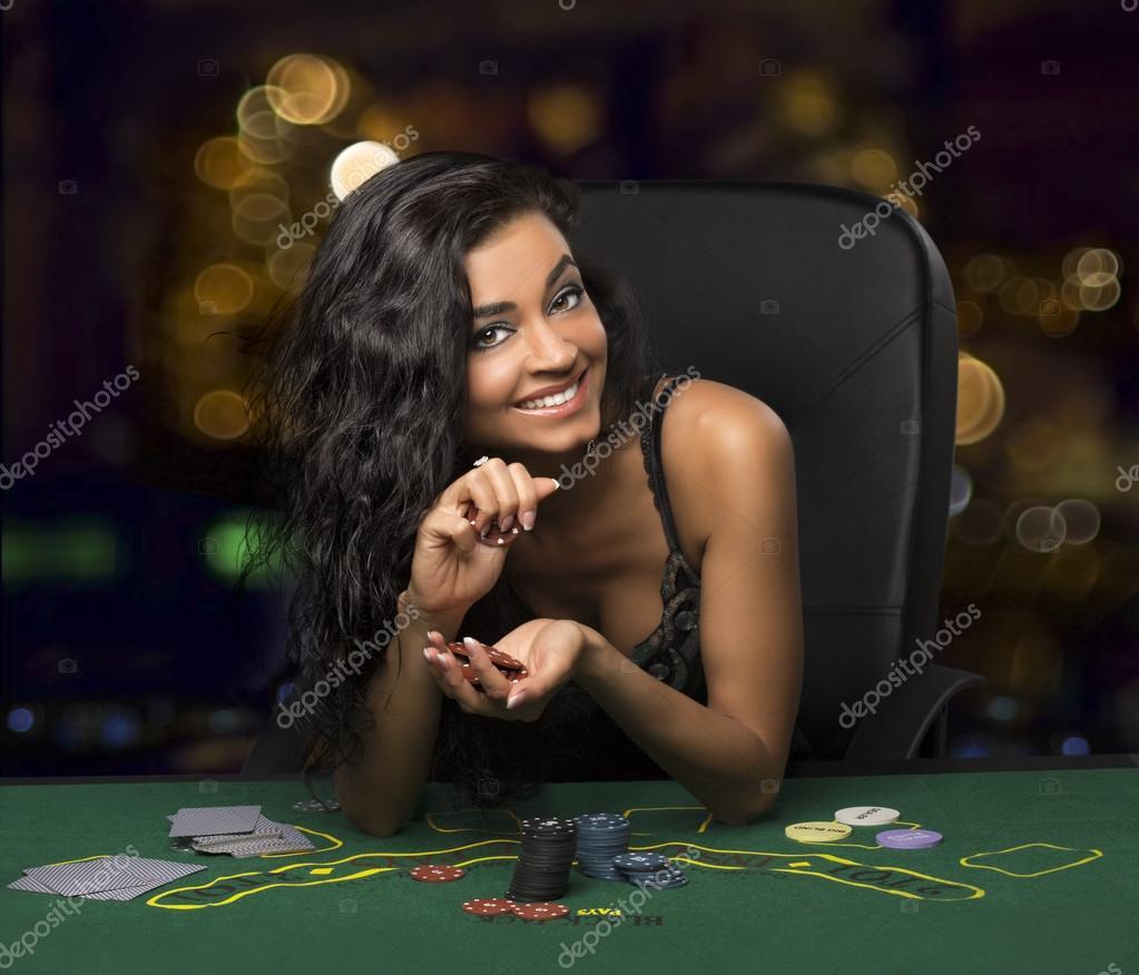 Brunette girl in the casino playing poker