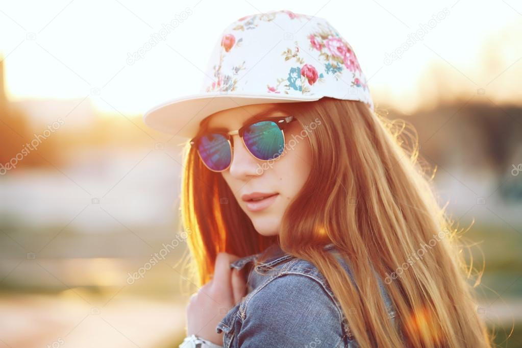 Plein air mode portrait de jeune fille swag élégant, port de cap de swag, lunettes  de soleil dernier cris et veste en Jean, vue imprenable sur la plage au ... 39fc08529dff