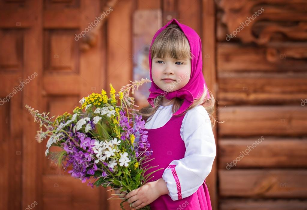 Slavic little girl in folk costume with a bouquet of wildflowers ...