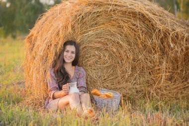 A smiling girl in a field of haystacks with a jug of milk
