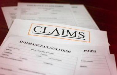 In selective focus of CLAIMS letter on white paper,at the middle of blurred Insurance Claim form,blurry light around
