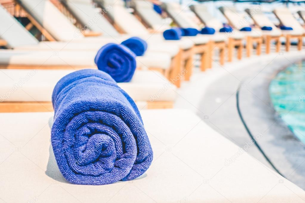 Towels pool on beds around swimming pool — Stock Photo ...