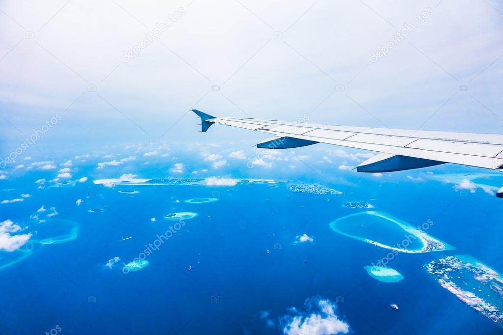 AIrplane wing with aerial view of maldives