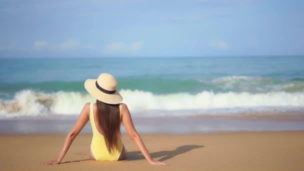 záběry krásné asijské ženy relaxační na pobřeží během letní dovolené