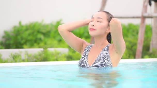 footage of Asian woman relaxing in pool during summer vacation