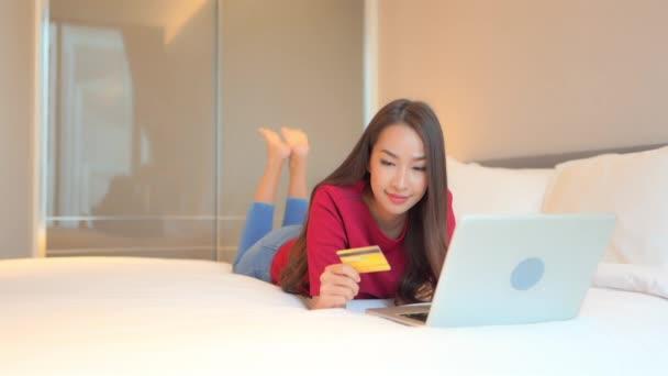 Filmaufnahmen der schönen jungen Asiatin beim E-Shopping mit dem Laptop, während sie es sich zu Hause auf dem Bett gemütlich macht