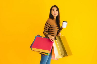 Beautiful young asian woman use smart mobile phone or cellphone with coffee cup and color shopping bag on yellow isolated background