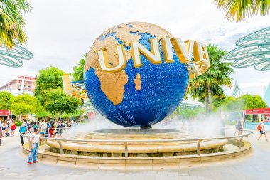 Tourists and theme park visitors taking pictures of the large rotating globe fountain in front of Universal Studios