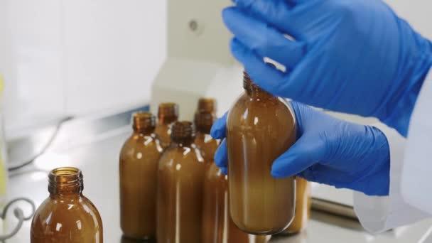 Kozmetológiai szakértő orvos gyógyszerész gyógyszerész gyógyszerész, aki kozmetikai orvoslást végez a laboratóriumban. természetes folyékony testápoló szérum öntése és mérése.Kozmetikum, illatszer gyártása.