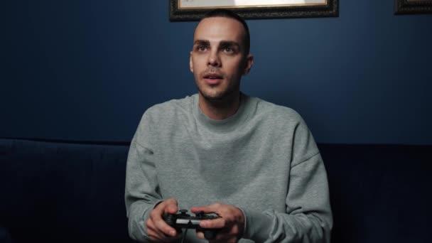 Vtipný nadšený mladý běloch hráč vítěz držení ovladače joystick hrát videohry sedí na pohovce doma. Muž hráč hraje videohry slaví vítězství.