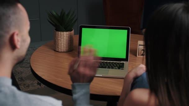 Junge Männer und Frauen im Home-Office-Geschäft mit grünem Laptop-Mock-up-Bildschirm, während sie auf der Couch im Wohnzimmer sitzen. Vergrößern Sie die Kamera aus der Rückansicht.