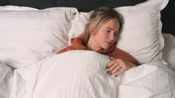 Top pohled na ženské problémy se spaním v ložnici. Krásná mladá žena, která má zlý sen. Žena s nespavostí. Poruchy spánku.