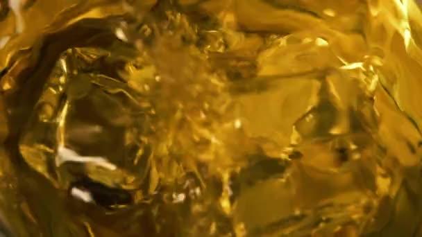 Makroaufnahme fallender Eiswürfel in Glas mit Whiskey. Zeitlupe plätschert dahin. Nahaufnahme. Rotation