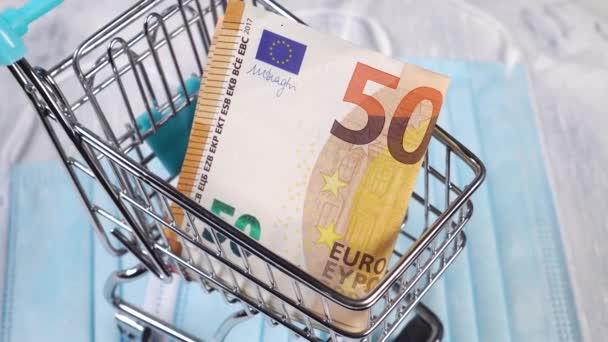 Nákupní košík s eurobankovkami na pozadí lékařských ochranných masek. Černý pátek koncepce a opatření na ochranu proti virům