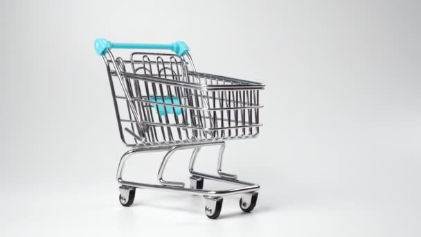 Empty supermarket trolley close-up on a white background. Consumerism and seasonal discounts concept