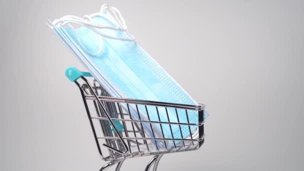 Mini supermarket vozík zblízka s lékařskými ochrannými maskami. Drolovací snímek