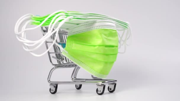 Shopping cart with bright medical protective masks on a white background. Close up. Medical supplies concept