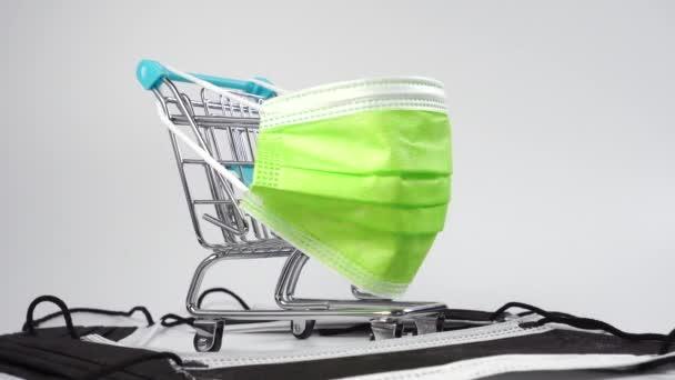 Szupermarket kocsi színes zöld védő orvosi maszk egy halom fekete higiéniai maszkok. Közelről. Dolly lőtt. Fogalmi miniatűr