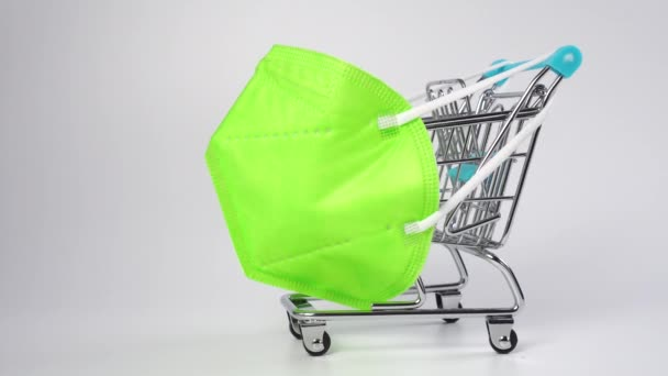 Protective medical mask KH95 on a shopping cart. Colorful green medical hygiene mask on a supermarket trolley. Close up. Dolly shot. Christmas Discounts and Black Friday Concept