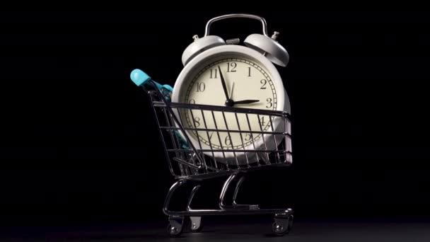 Nákupní košík s analogovými hodinami v kovovém lesklém koši na černém pozadí. Detailní záběr. Koncept Černého pátku