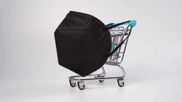 Supermarket trolley with black medical protective mask KN95 closeup on a white background. Shiny metal basket. Christmas Discount Week Concept