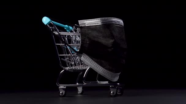 Supermarket trolley in miniature with a black medical protective mask on a black background close-up. Protected Black Friday concept. Dolly Shot